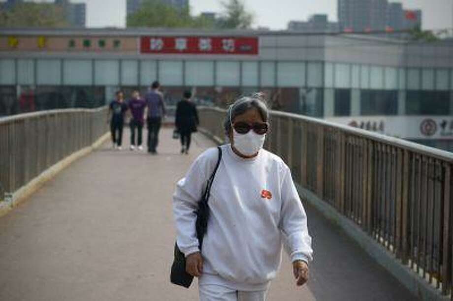 An elderly woman wears a face mask as she walks on an overpass in Beijing on May 2, 2013. Photo: AFP/Getty Images / 2013 AFP