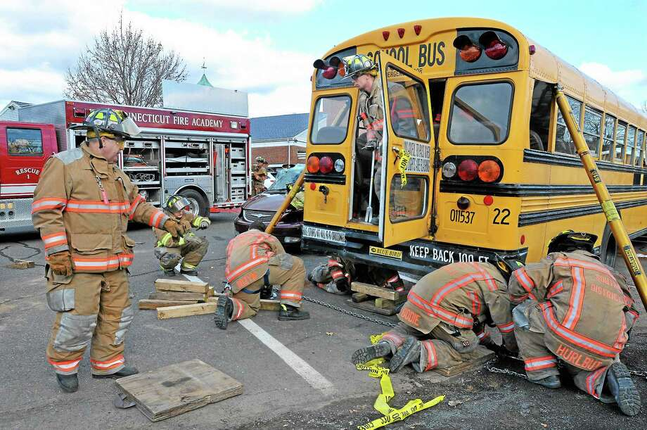 South District firefighters stabilize a school bus as part of a week-long training program during which they simulate vehicle crash scenarios. The program is funded by a grant from FEMA. Photo: Catherine Avalone - The Middletown Press   / TheMiddletownPress