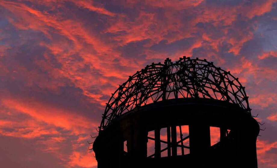 The Atomic Bomb Dome is silhouetted at sunset in Hiroshima, western Japan,  Monday, Aug. 5, 2013. Hiroshima marks the 68th anniversary of the world's first atomic bombing Tuesday.(AP Photo/Shizuo Kambayashi) Photo: ASSOCIATED PRESS / AP2013