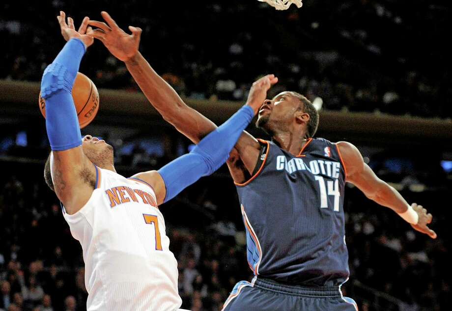 The Bobcats' Michael Kidd-Gilchrist, right, slaps the ball away from the Knicks' Carmelo Anthony during the first quarter of Tuesday's game in New York. Photo: Bill Kostroun — The Associated Press  / FR51951 AP