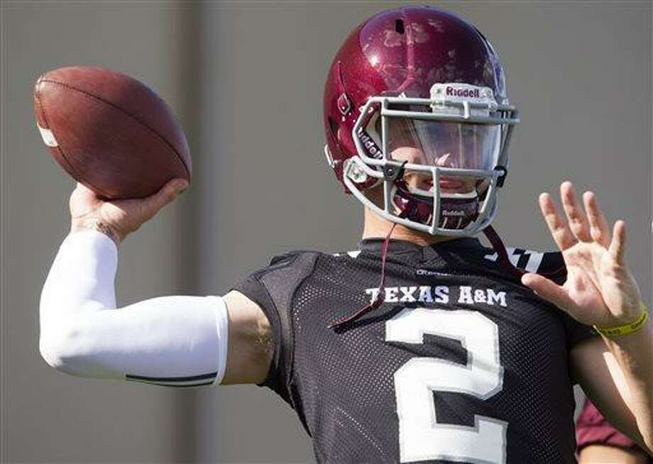 Texas A&M quarterback and Heisman Trophy winner Johnny Manziel throws during football practice, Monday, Aug. 5, 2013, in College Station, Texas. The NCAA has started an investigation as to whether Manziel received payment for signing hundreds of autographs on photos and sports memorabilia in January. (AP Photo/Patric Schneider) Photo: AP / FR170473 AP