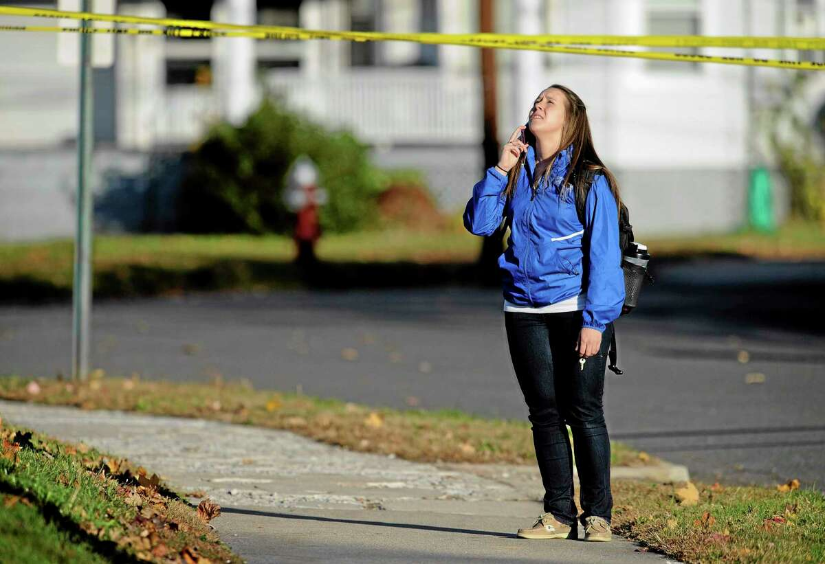A student waits to return to campus following a lockdown due to a sighting of an armed man at Central Connecticut State University, Monday, Nov. 4, 2013, in New Britain, Conn. Officials say one person is in custody. (AP Photo/Jessica Hill)
