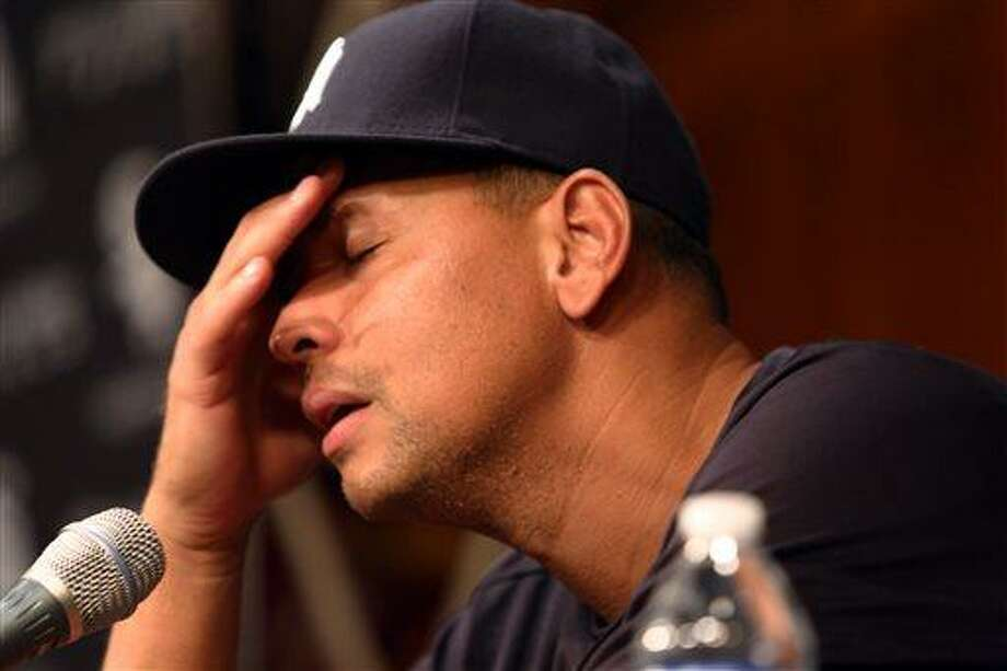 New York Yankees' Alex Rodriguez, with his hand to his head, talks during a news conference before the Yankees play the Chicago White Sox in a baseball game at US Cellular Field in Chicago on Monday, Aug. 5, 2013. Rodriguez was suspended through 2014 and All-Stars Nelson Cruz, Jhonny Peralta and Everth Cabrera were banned 50 games apiece Monday when Major League Baseball disciplined 13 players in a drug case, the most sweeping punishment since the Black Sox scandal nearly a century ago. (AP Photo/Charles Cherney) Photo: AP / FR170067 AP