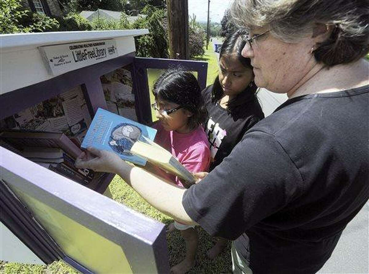 In this July 23, 2013 photo, Mary Fournier and her daughters Jenna,10, center, and Olivia, 13, look at new books in their Little Free Library in front of their Hillside Ave., home in Enfield Conn. The books are stored in what is essentially an oversized mailbox on Fournier?s front lawn. Those who are interested can borrow or donate a book at no cost and without a membership card, and can keep the book for as long as they need to. (AP Photo/Journal Inquirer, Jim Michaud) MANDATORY CREDIT