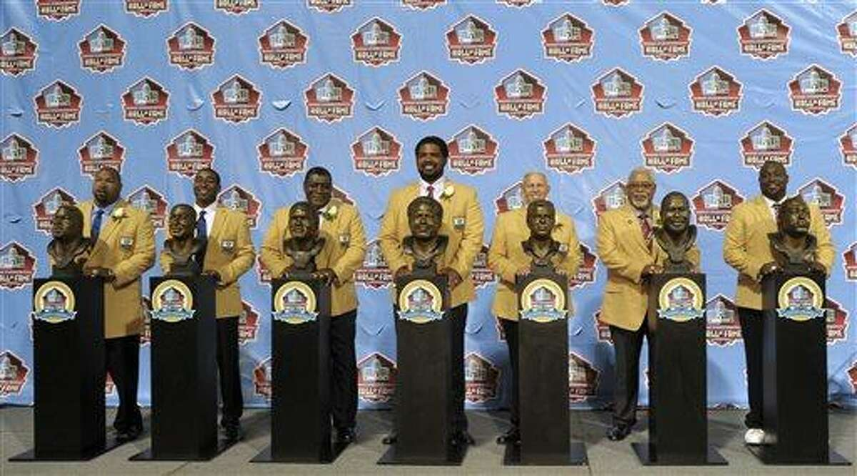 Hall of Fame inductees, from left, Larry Allen, Cris Carter, Dave Robinson, Jonathan Ogden, Bill Parcells, Curley Culp and Warren Sapp pose with their bronze busts during the 2013 Pro Football Hall of Fame Induction Ceremony Saturday, Aug. 3, 2013, in Canton, Ohio. (AP Photo/David Richard)