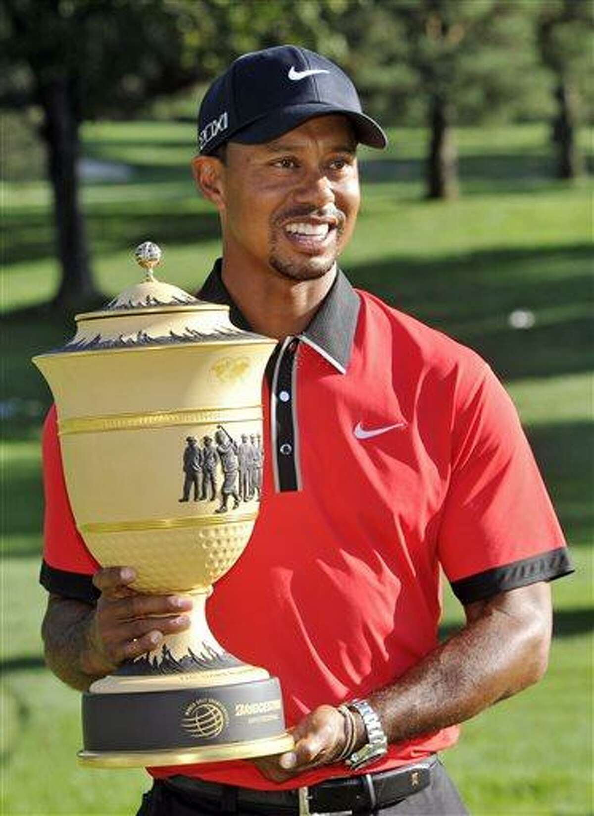 Tiger Woods holds the trophy after winning the Bridgestone Invitational golf tournament Sunday, Aug. 4, 2013 at Firestone Country Club in Akron, Ohio. (AP Photo/Phil Long)