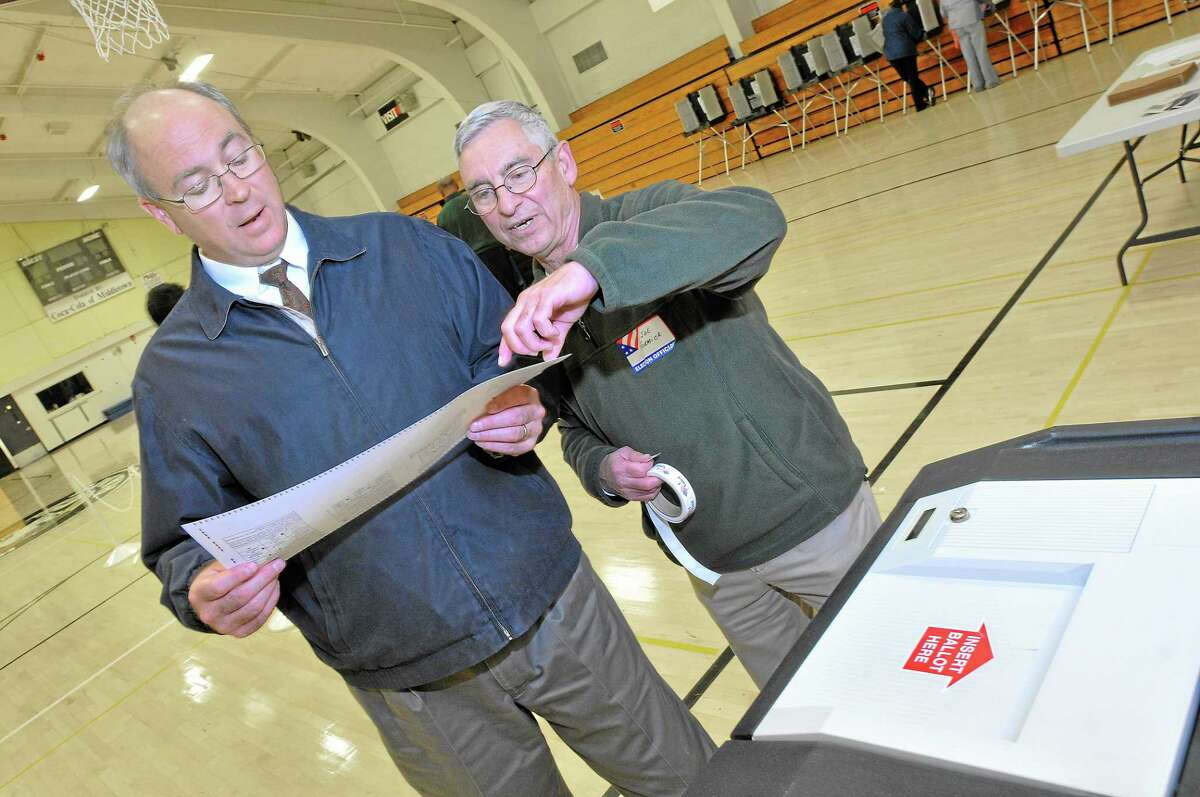 Machine tender Joe Formica tells Craig Nielsen, a voter in District 11 that he has to fill out a new ballot. The optical scanner would not accept Nielsen's ballot, he voted for more than 8 council members.