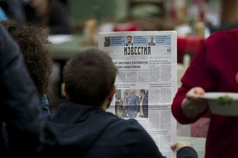 "A street cafe visitor reads a fresh Russian newspaper ""Izvestia"" with a front page pictures of Russian lawyer Anatoly Kucherena, center, and National Security Agency leaker Edward Snowden, center left, taken on Thursday, Aug. 1, 2013 at Sheremetyevo airport outside Moscow, Russia, on Friday, Aug. 2, 2013. Snowden has received asylum in Russia for one year and left the transit zone of Moscow's airport, his lawyer said Thursday. Kucherena said after meeting with the fugitive at Moscow's Sheremetyevo airport, where he was stuck since his arrival from Hong Kong on June 23, that he handed him the papers proving his status. Kucherena said that Snowden's whereabouts will be kept secret for security reasons.  (AP Photo/Alexander Zemlianichenko) Photo: AP / AP"