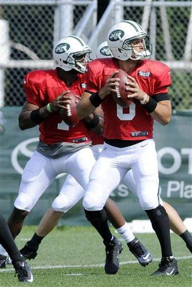 New York Jets quarterbacks Mark Sanchez, right, and Geno Smith drop back at their NFL football training camp Monday, July 29, 2013, in Cortland, N.Y. (AP Photo/Bill Kostroun) Photo: AP / FR51951 AP