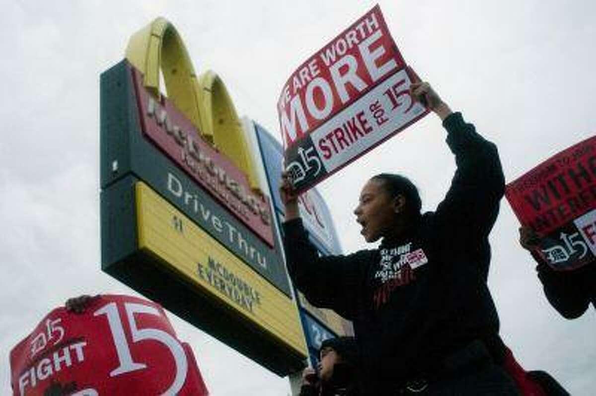Fast-food worker Michelle Osborn, 23, of Flint shouts out chants as she and a few dozen others strike outside of McDonald's on Wednesday, July 31, 2013 in Flint.