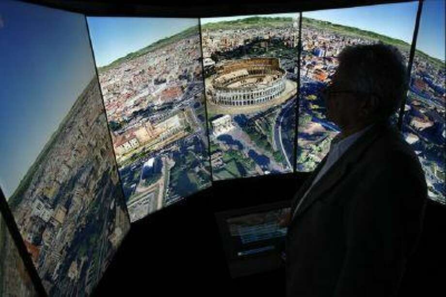 A visitor looks at a three-dimensional rendering of Rome while using Google Earth software at the official opening party of the Google offices in Berlin.