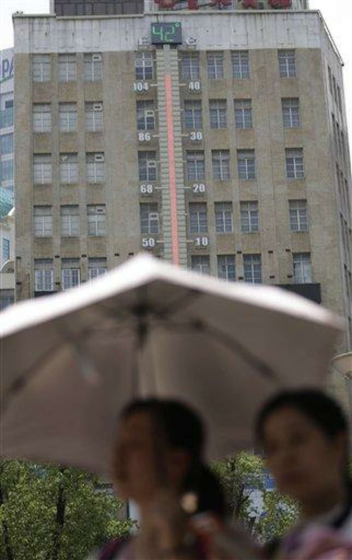 Women walk near a giant thermometer on the building which indicates the current highest temperature in Shanghai, China, Thursday, Aug. 1, 2013. Hot weather has set in with temperatures rising up to 40 degrees Celsius (104 degrees Fahrenheit) in Shanghai. (AP Photo/Eugene Hoshiko)