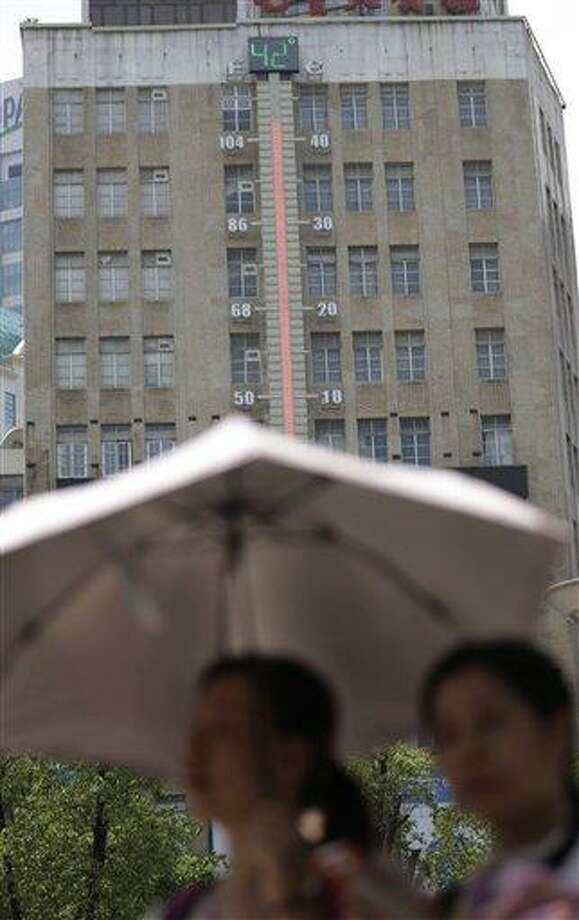 Women walk near a giant thermometer on the building which indicates the current highest temperature in Shanghai, China, Thursday, Aug. 1, 2013.  Hot weather has set in with temperatures rising up to 40 degrees Celsius (104 degrees Fahrenheit) in Shanghai. (AP Photo/Eugene Hoshiko) Photo: AP / AP