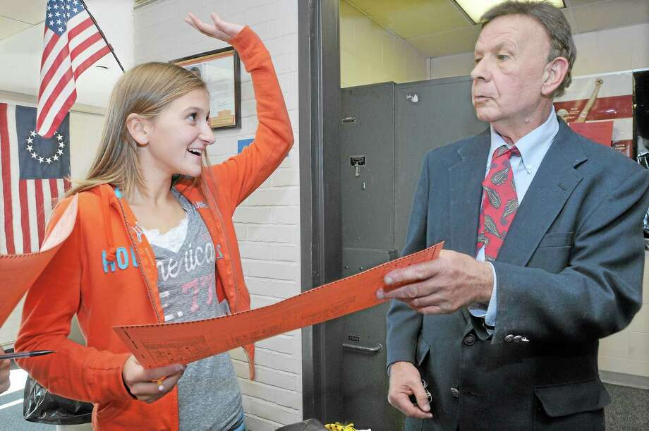 "Alina Williamson, 13, an eighth-grade Woodrow Wilson Middle School student, raises her hand in response to Orlando Zacchio's question, ""Who has met Mayor Dan Drew?"" Zacchio (right) visited the school Monday to talk about the annual straw poll, which teaches kids about voting but also fairly accurately predicts election winners. Zacchio started the Middletown straw poll for a school project in 1963. Photo: Catherine Avalone - The Middletown Press   / TheMiddletownPress"