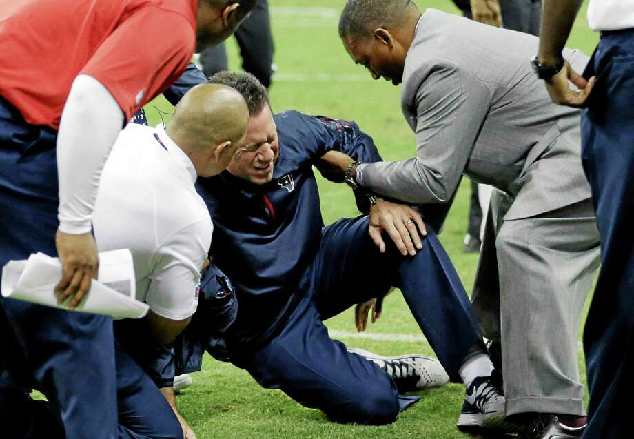 Houston Texans head coach Gary Kubiak, center, his helped after he collapsed on the field during the second quarter Sunday in Houston. Photo: David J. Phillip — The Associated Press  / AP