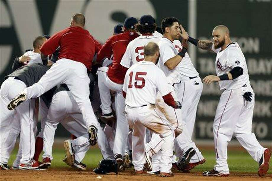 The Boston Red Sox including Jonny Gomes, right, Jacoby Ellsbury, second from right, and Dustin Pedroia (15) celebrate after a walkoff-single by Daniel Nava that scored Pedroia in the ninth inning of a baseball game against the Seattle Mariners in Boston, Thursday, Aug. 1, 2013. The Red Sox won 8-7. (AP Photo/Michael Dwyer) Photo: AP / AP