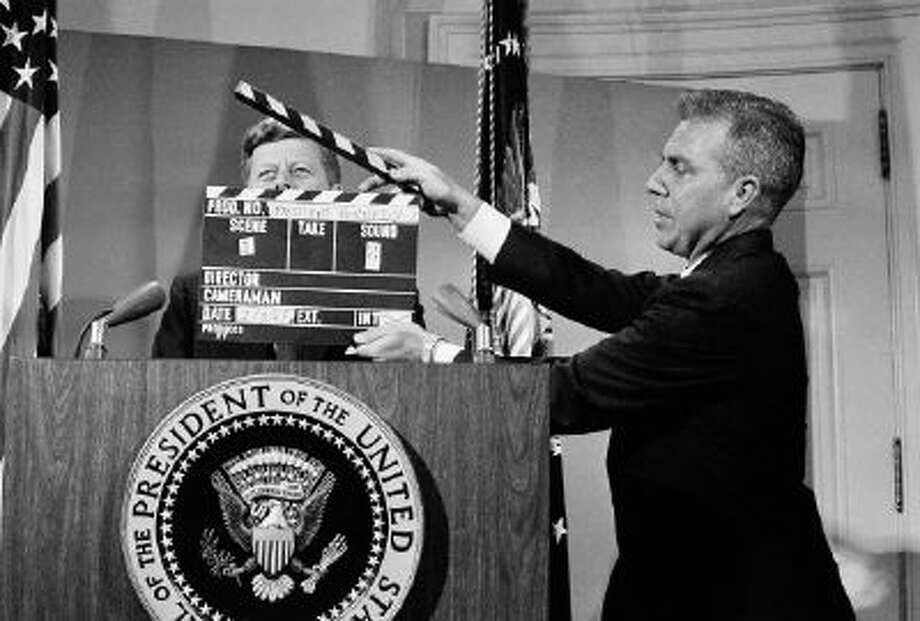 In this July 3, 1963 file photo, U.S. President John F. Kennedy stands at the lectern behind a production slate board during a television taping at the White House. In life and especially in death, Kennedy changed television forever.
