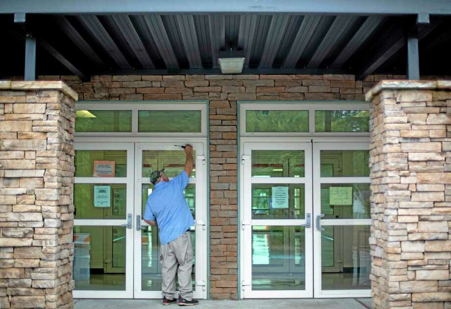 Carpenter William Brooks secures a piece of plexiglass to the front door of the Ronald E. McNair Discovery Learning Academy where a glass panel was shot out during an exchange of gunfire Tuesday between police and a man who entered the school with an assault rifle, Wednesday, Aug. 21, 2013, in Decatur, Ga. (AP Photo/David Goldman) Photo: AP / AP