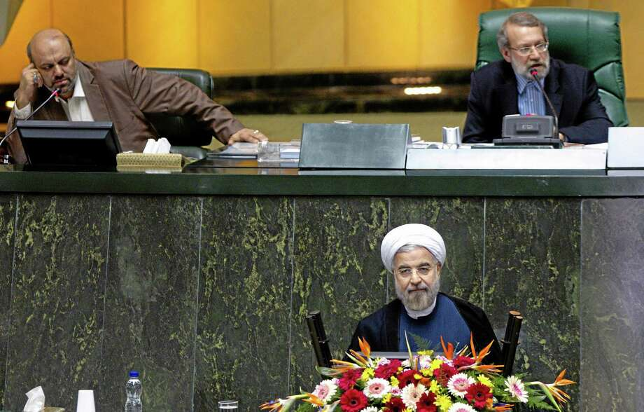 Iranian President Hasan Rouhani, bottom, listens during a parliament session to defend the nominees for the three remaining ministries of his cabinet while parliament speaker Ali Larijani speaks, top right, in Tehran, Iran, Sunday, Oct. 27, 2013. Iran's parliament has rejected a close ally of Rouhani for a ministerial post. In a vote Sunday, 141 out of 261 lawmakers present voted against Reza Salehi Amiri, who Rouhani nominated as sports and youth minister. (AP Photo) Photo: AP / AP