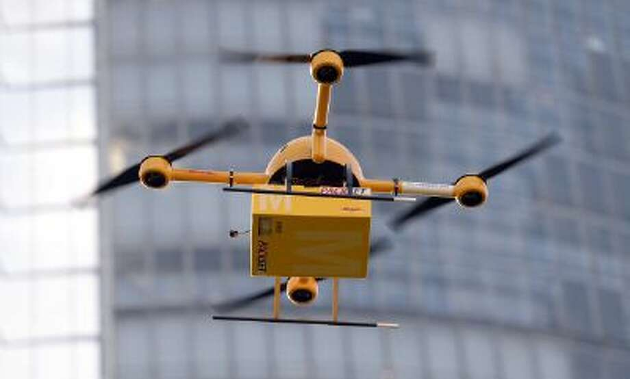 A quadrocopter drone controlled remotely transports a post package during a test flight for the Deutsche Post DHL in Bonn, western Germany. The Deutsche Post tests a system for delivering urgent packages via drone over short distances. Photo: AFP/Getty Images / 2013 AFP