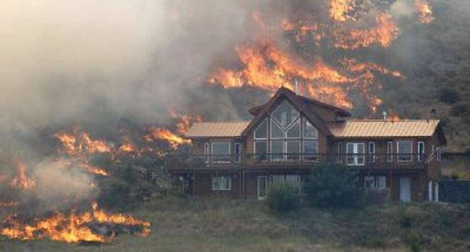 In this photo taken Tuesday, Aug. 14, 2012, flames surround a house on a hillside above Bettas Road near Cle Elum, Wash.