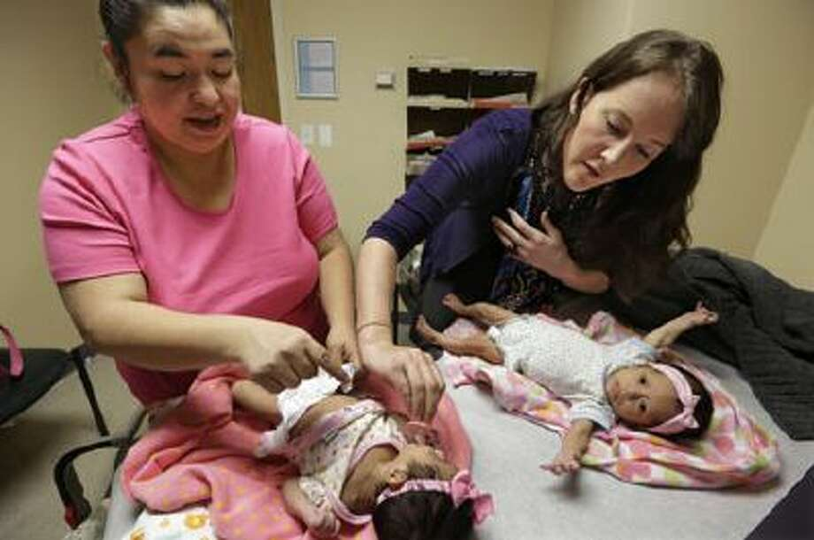 In this March 28, 2013 file photo, medical resident Stephanie Place examines two-month-old twins Abigale, left, and Valeria Lopez as their mother Carolina Lopez, left, helps, at the Erie Family Health Center in Chicago. Photo: AP / AP2013