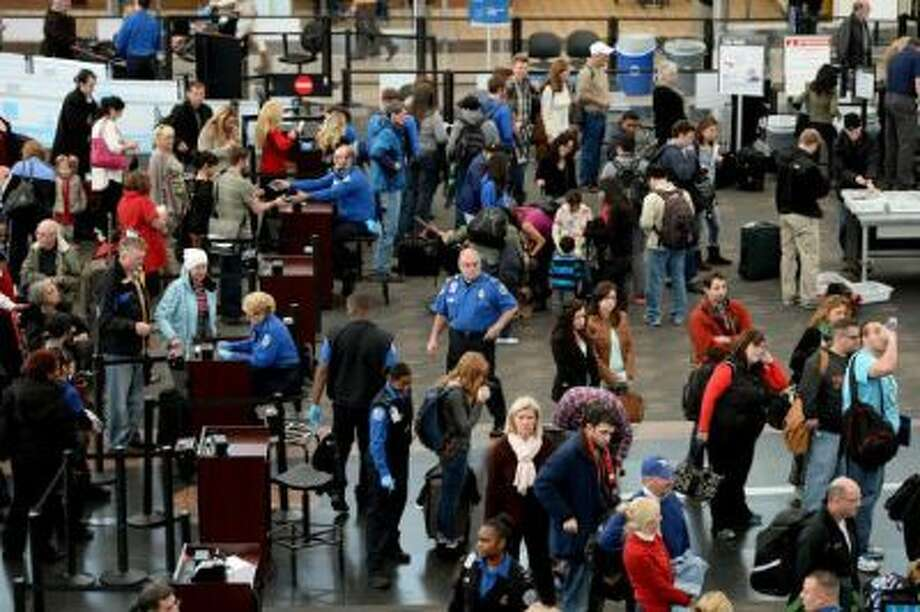 Travelers line up for a security checkpoint at DIA. The airport will ban marijuana possession but doesn't plan to actively enforce the policy.