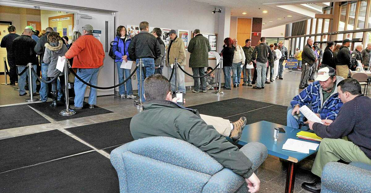 In this Dec. 27, 2013 photo, gun owners wait in line at the State of Connecticut Department of Public Safety office in Middletown, Conn., to renew hand gun permits, and register firearms classified as assault weapons prior to the Jan. 1 deadline. The new regulations were enacted in April in response to the Sandy Hook Elementary School shooting. (AP Photo/The Middletown Press, Catherine Avalone)