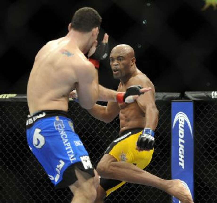 Anderson Silva, right, of Brazil, prepares to kick Chris Weidman of Baldwin, N.Y., during the UFC 168 mixed martial arts middleweight championship bout on Saturday, Dec. 28, 2013, in Las Vegas.