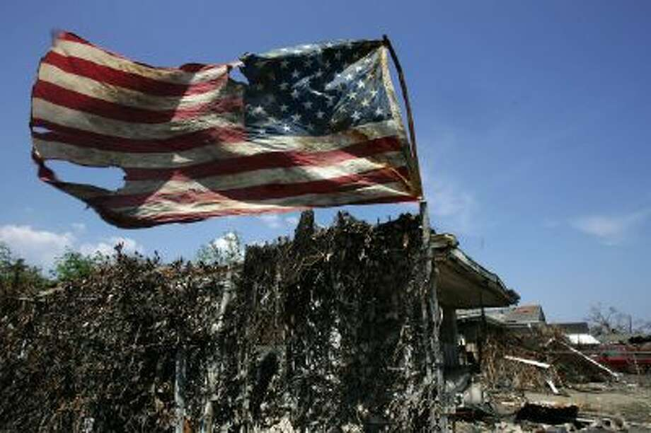 A tattered US flag waves on a pole in the devastated Ninth Ward of New Orleans on Sept. 21, 2005, following Hurricane Katrina.