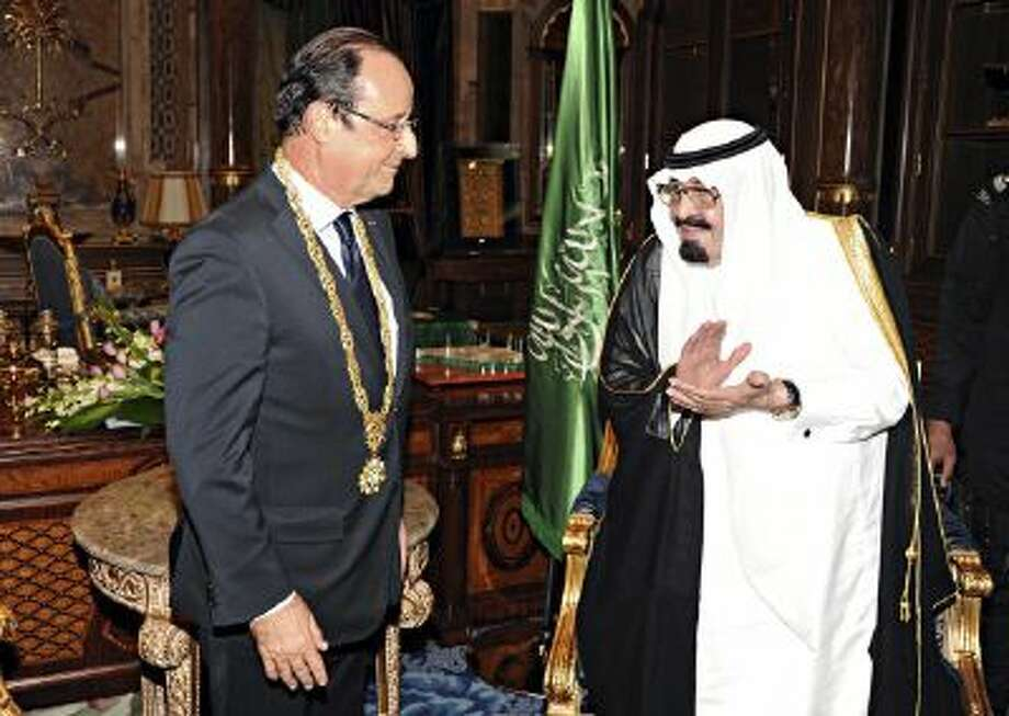 In this Nov. 4, 2012 file photo released by Saudi Press Agency, King Abdullah of Saudi Arabia, right, applauds French President Francois Hollande, left, after presenting him with the Order of Merit in Jiddah, Saudi Arabia.