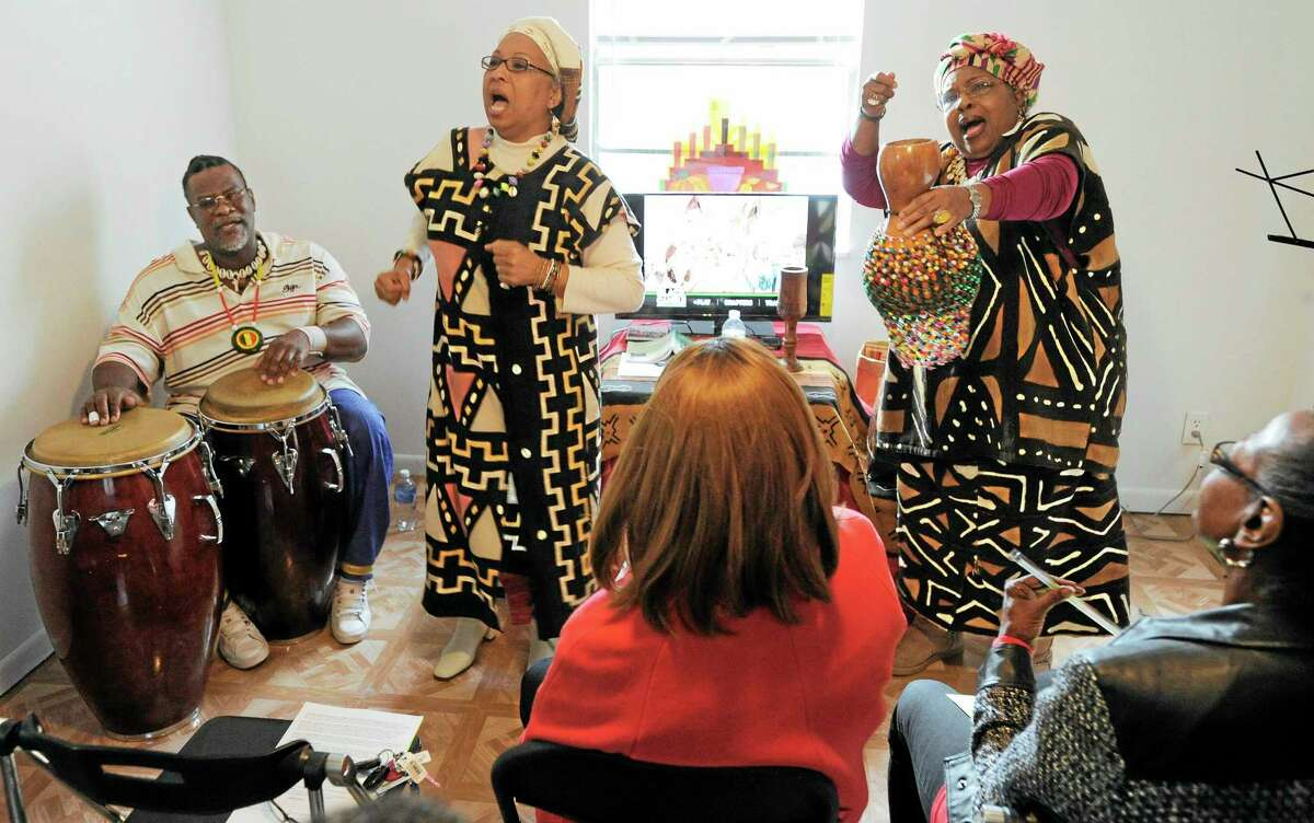With Jose Palma, left, on the drums, Ok Sun Burks, center, and Frances Bradley perform Yoruba folk songs during a Kwanzaa celebration Thursday, Dec. 26, 2013, in Starke, Fla. (AP Photo/The Florida Times-Union, Bob Self)
