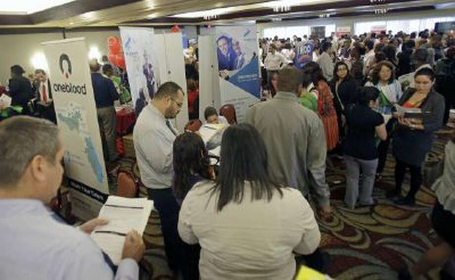 This Aug. 14, 2013 file photo shows job seekers checking out companies at a job fair in Miami Lakes, Fla.