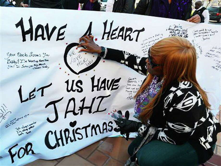 Dede Logan, of Oakland, adds red stars to a poster in support of Jahi McMath in front of Children's Hospital Oakland in Oakland, Calif., on Monday, Dec. 23, 2013. McMath was declared brain dead after experiencing complications following a tonsillectomy at the hospital. (AP Photo/The Contra Costa Times-Bay Area News Group, Susan Tripp Pollard) Photo: ASSOCIATED PRESS / CONTRA COSTA TIMES2013