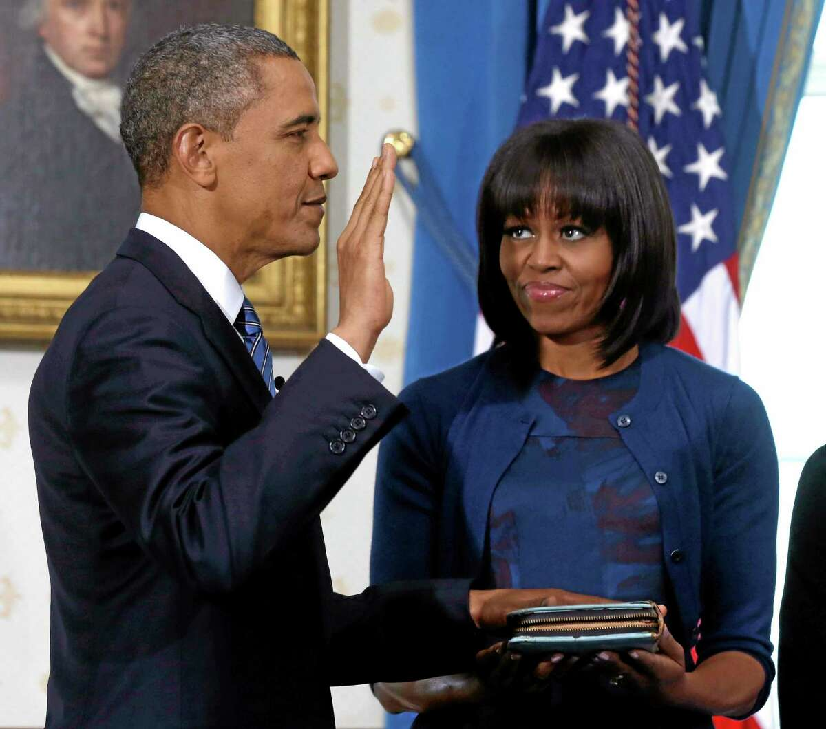 FILE - This Jan. 20, 2013 file-pool photo shows President Barack Obama officially sworn-in by Chief Justice John Roberts, not pictured, in the Blue Room of the White House in Washington, Sunday, Jan. 20, 2013, as first lady Michelle Obama, holds the Robinson Family Bible. It was a moment for Barack Obama to savor. His second inaugural address over, Obama paused as he strode from the podium last January, turning back for one last glance across the expanse of the National Mall, where a supportive throng stood in the winter chill to witness the launch of his new term.