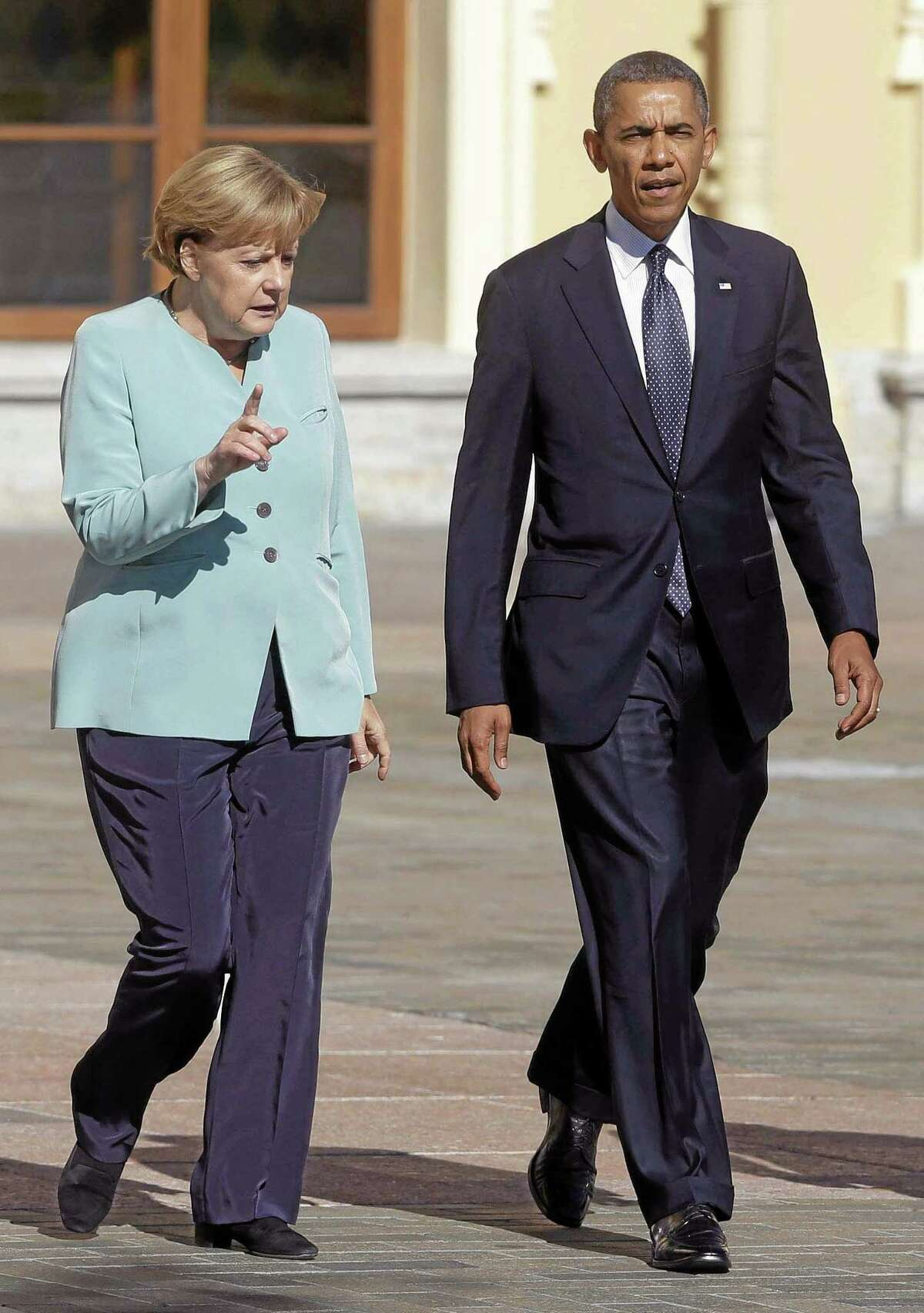FILE - In this Sept. 6, 2013 file photo, President Barack Obama walks with German Chancellor Angela Merkel prior to the group photo at the G-20 summit at the Konstantin Palace in St. Petersburg, Russia. It was a moment for Barack Obama to savor. His second inaugural address over, Obama paused as he strode from the podium last January, turning back for one last glance across the expanse of the National Mall, where a supportive throng stood in the winter chill to witness the launch of his new term.