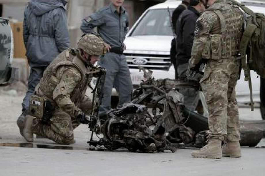 NATO forces examine the remains of a car after a suicide car bomb attack on the Jalalabad-Kabul road in Kabul, Afghanistan, Friday, Dec. 27, 2013.