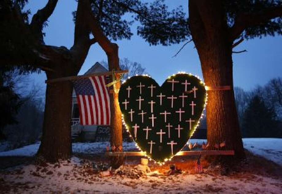 - In this Saturday, Dec. 14, 2013, file photo, a makeshift memorial with crosses for the victims of the Sandy Hook massacre stands outside a home in Newtown, Conn.,