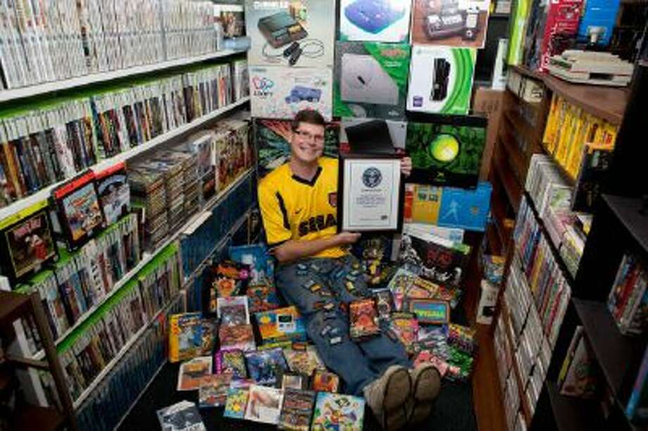 Michael Thomasson poses in the basement of his suburban Buffalo home, where he stores his collection of video games.