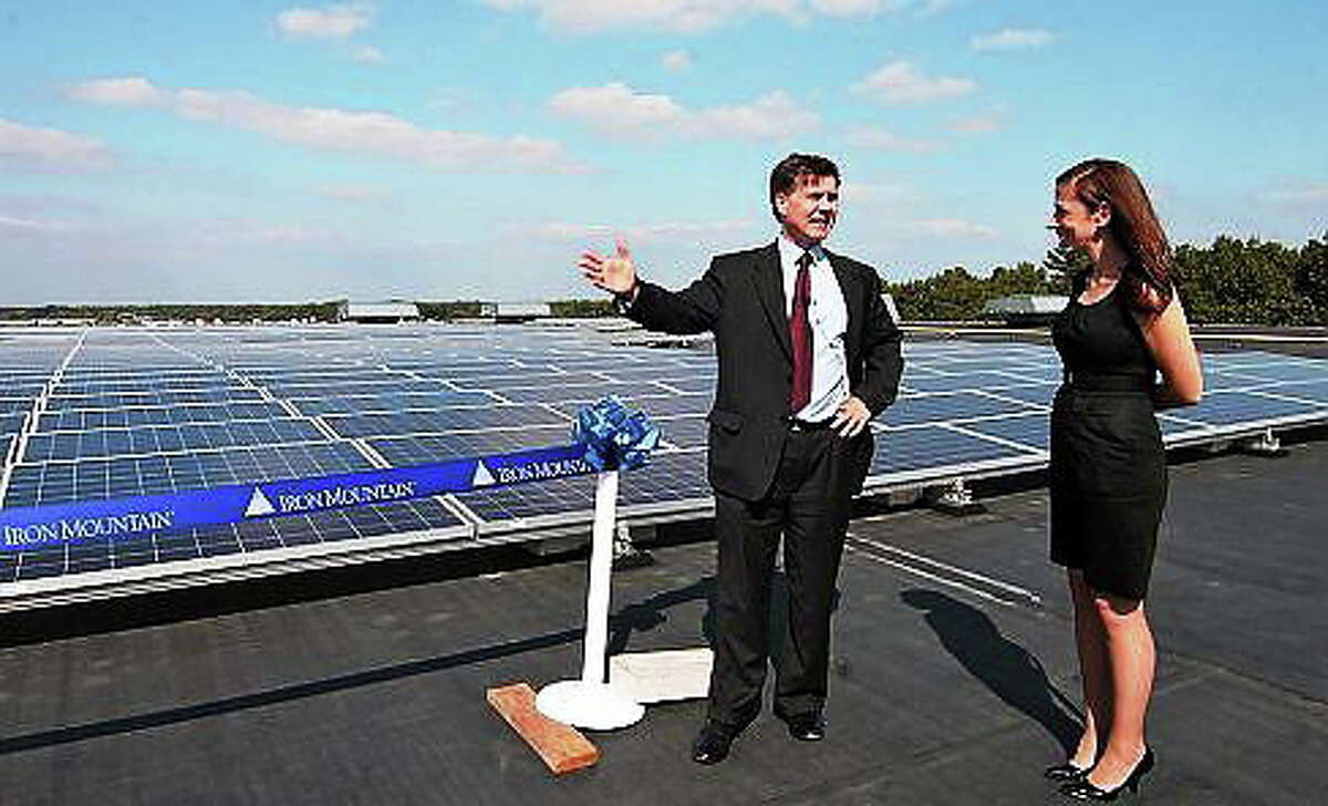 DEEP Commissioner Daniel C. Esty and Iron Mountain Director of Corporate Responsibility and Sustainability Samantha Joseph prepare to cut the ribbon on an unrelated 902-panel solar array in Windsor on Oct. 2, 2013. Doug Hardy/CT NewsJunkie file photo