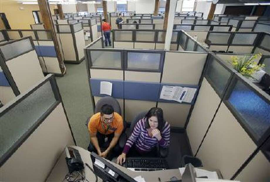 Workers stay busy Sept. 27 in one of many cubicles at a center in St. Paul, Minn., in preparation for delivering changes tied to the federal health care law opens for enrollment. Photo: AP / AP