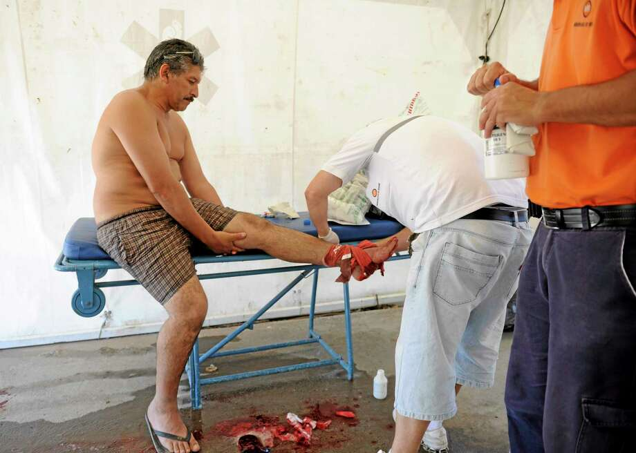 A man is treated after he was bit by a palometa, a type of piranha, while wading in the Parana River in Rosario, Argentina, Wednesday, Dec. 25, 2013. Lifeguards director Federico Cornier said Thursday that thousands of bathers were cooling off from 100 degree temperatures in the Parana River on Wednesday when bathers suddenly came to them complaining of bite marks on their hands and feet. He blamed the attack on palometas, îa type of piranha, big, voracious and with sharp teeth that can really bite.î (AP Photo/La Capital, Silvina Salinas) Photo: AP / La Capital