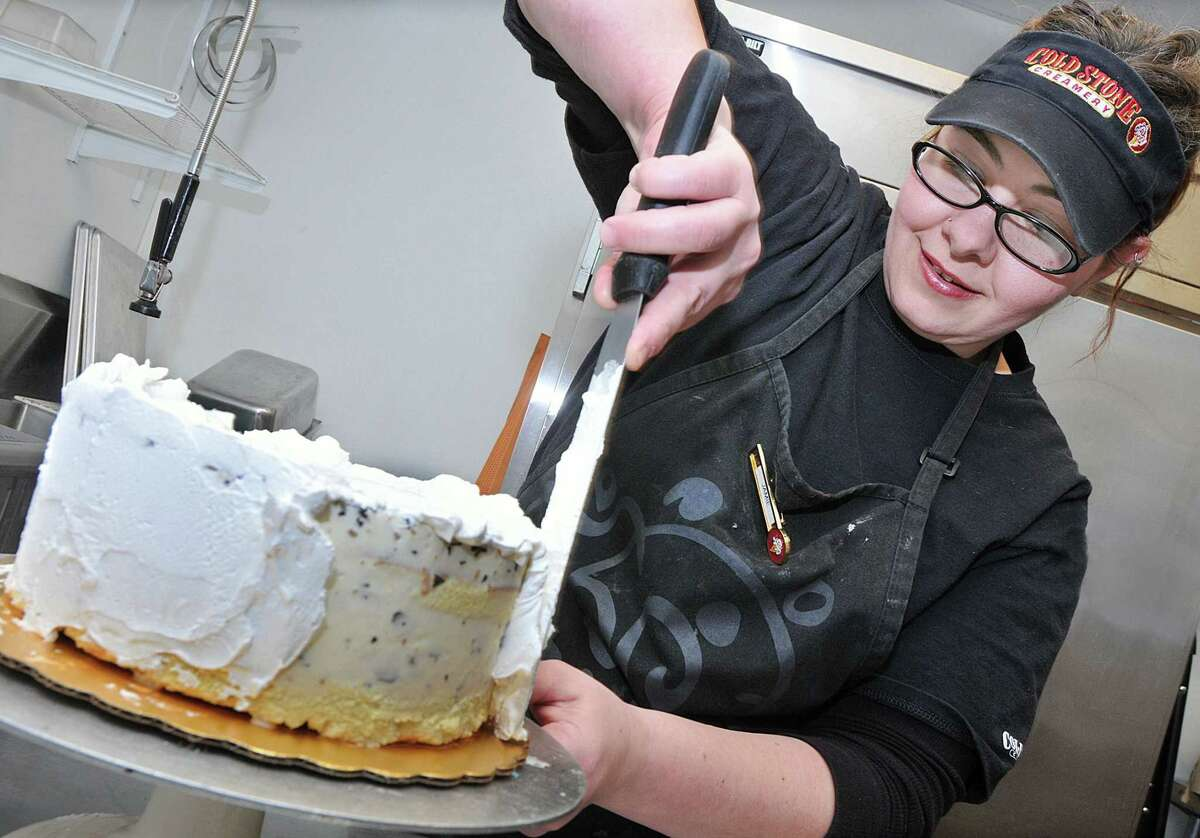 Jamie Datino, an ice cream cake designer at Cold Stone Creamery in Middletown spreads Bettercreme frosting on a cake Thursday afternoon. Catherine Avalone - The Middletown Press