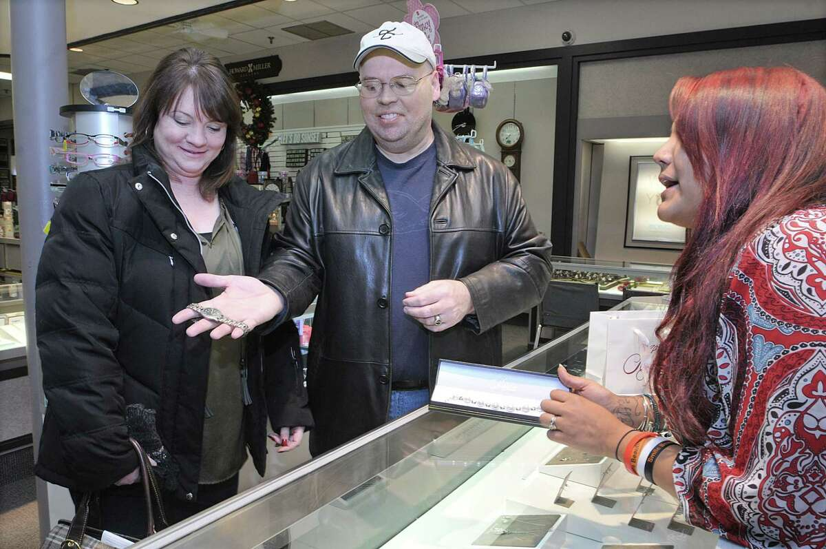 Pooja St. Amand, a sales associate at Mallove Jewelers in Middletown, finishes up an exchange with Jacquie Doberski and Phil Hartmann Thursday evening. Hartmann, formerly of Middletown, purchased a pearl bracelet for his girlfriend who decided to exchange the bracelet and buy Hartmann a Seiko watch.