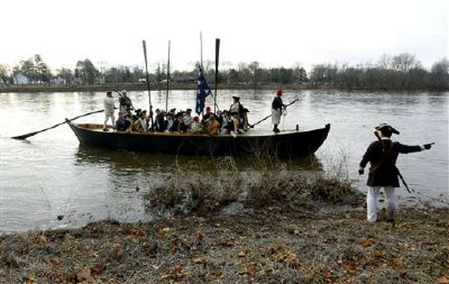 A boat containing George Washington, played by John Godzieba, approaches the riverbank on the New Jersey side after a crew of re-enactors crossed the Delaware River from Pennsylvania during the 61st annual re-enactment of Washington's daring Christmas 1776 river crossing. Photo: AP / AP