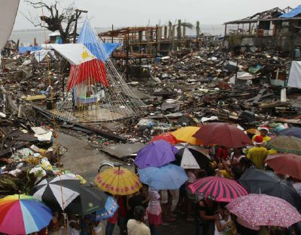 Typhoon survivor child's line up for receive a give from donations during Christmas at a devastated area in Tacloban, Philippines, Wednesday.