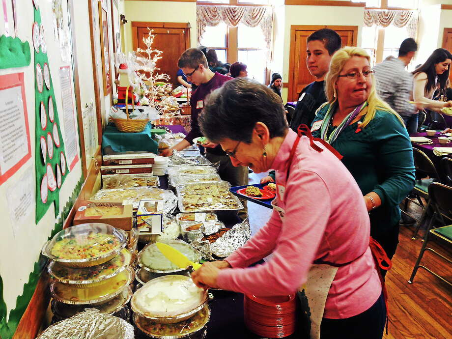 Michael T. Lyle Jr. - The Middletown Press  Volunteers assist with serving guests attending The First Church of Christ's annual Christmas dinner festivities on Wednesday in Middletown. Photo: Journal Register Co.