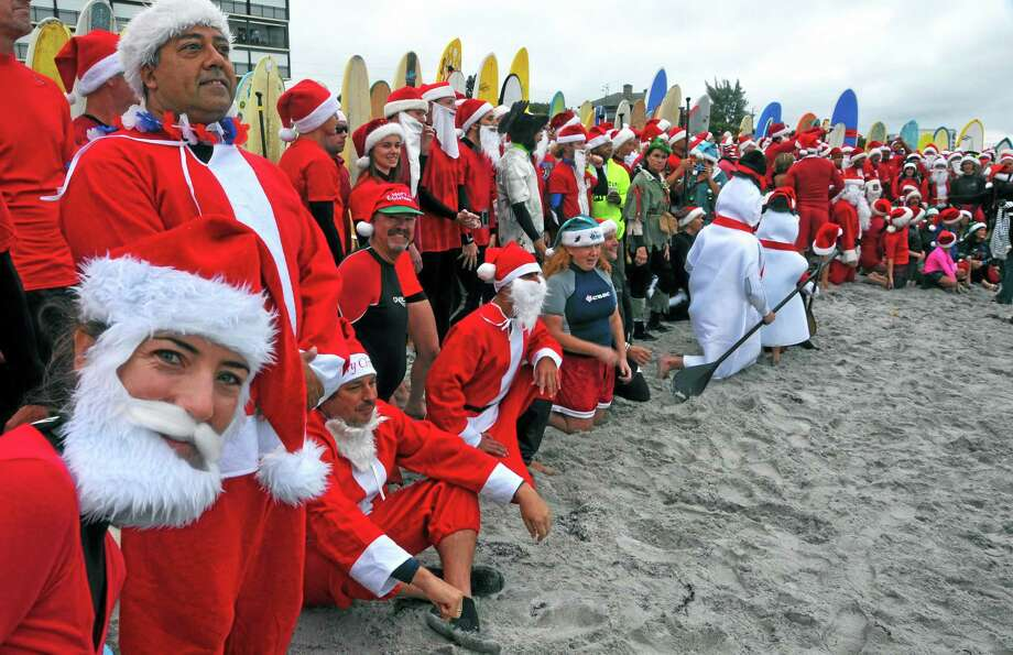 """Shaylona Kirk, of Cocoa Beach, left, peeks at the camera during the photo shoot of over 210 surfers dressed as Santa Claus, elves and snowmen at the fourth annual """"surfing Santas"""" event in Cocoa Beach, Fla. Organizer George Trosset said he may move the holiday event to downtown Cocoa Beach next year to accommodate growing crowds. He started the tradition in 2009 with a few family members after seeing a television commercial featuring people surfing in Santa Claus attire. AP Photo/Florida Today, Malcolm Denemark Photo: AP / Florida Today"""
