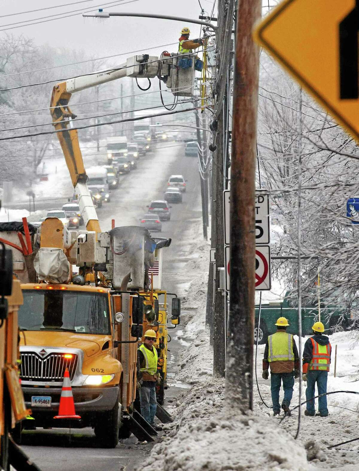 Utility crews respond to a downed power line at the intersection of Dorset Street and Kennedy Drive in South Burlington, Vt., on Monday, Dec. 23, 2013. From Michigan to Maine, hundreds of thousands remain without power days after a massive ice storm _ which one utility called the largest Christmas-week storm in its history _ blacked out homes and businesses in the Great Lakes and Northeast. (AP Photo/Burlington Free Press, Glenn Russell)