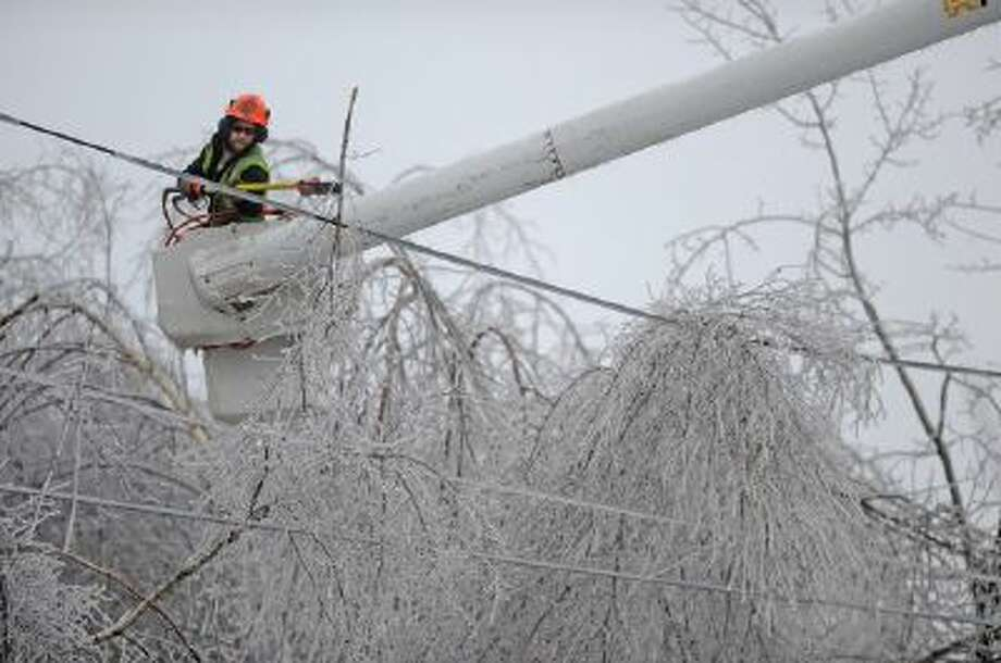 Andrew Powers clears power lines from iced branches in Waterville, Maine, on Monday.